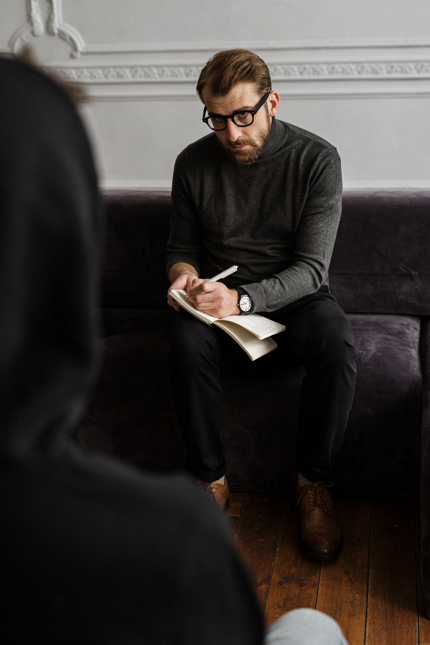 A bespectacled man takes notes as he sits on a plush couch in front of a person in a hoodie.
