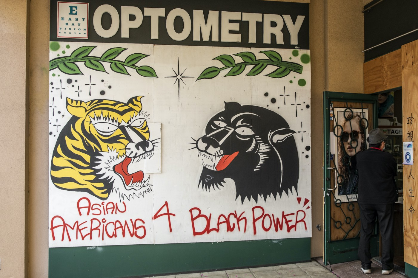 "Mural: A tiger and a panther, branches, and sparkles above the text ""Asian Americans 4 Black power."""