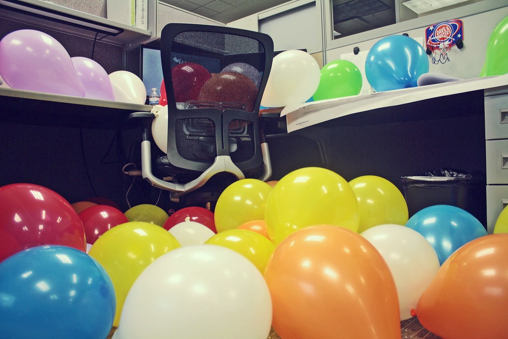 An office cubicle filled with balloons