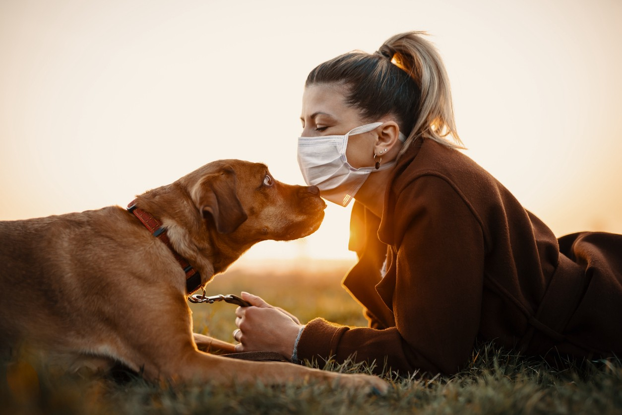 Woman wearing a protective mask is walking alone with a dog outdoors because of the corona virus pandemic covid-19.