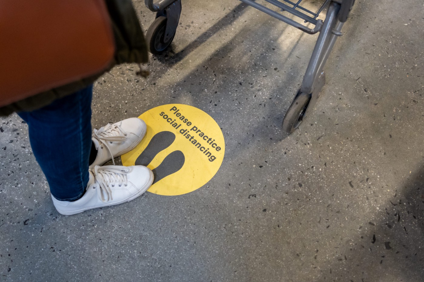 """A photo of a person standing on a sticker that says """"practice social distancing"""" at a grocery store."""