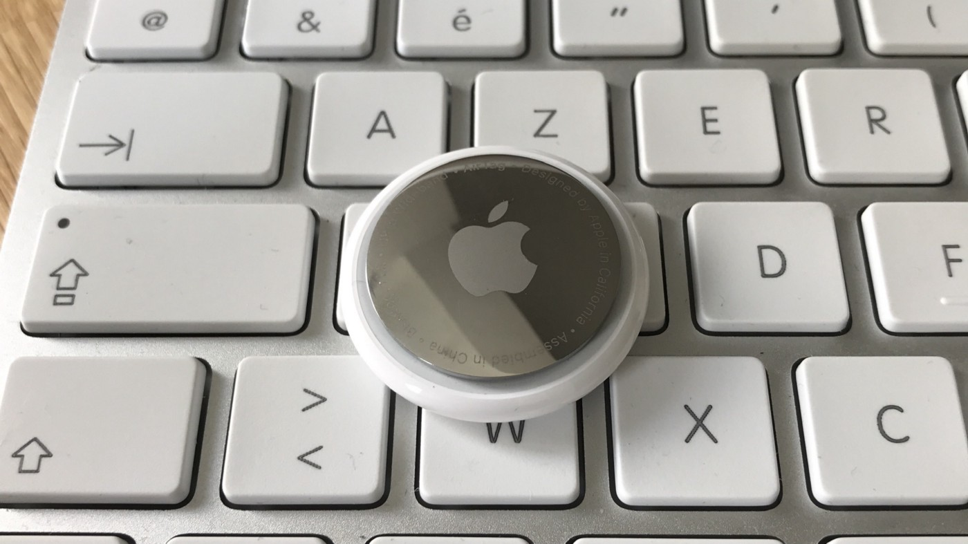 Apple Airtag placed on an Apple wireless keyboard.