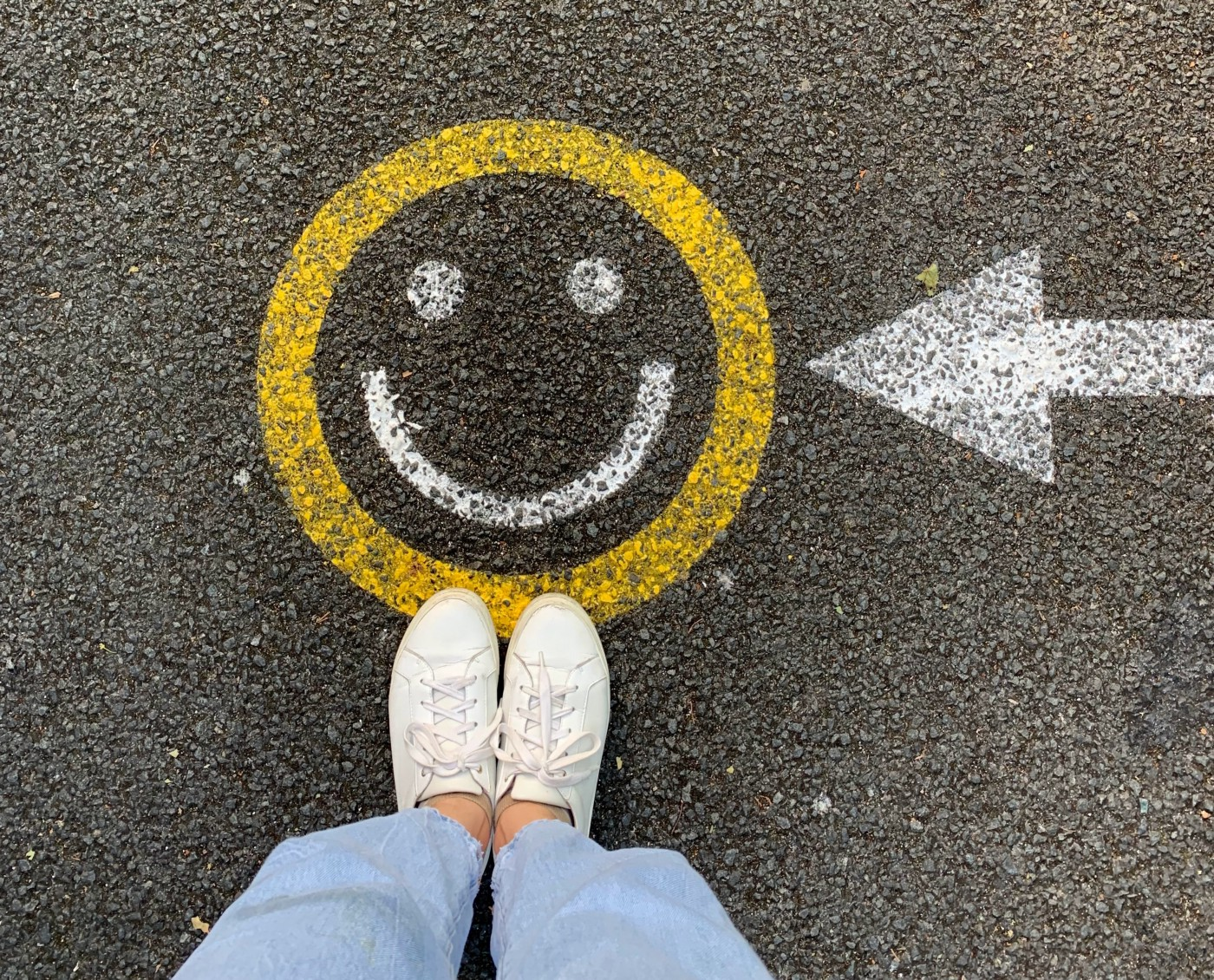 Person standing on a street with an arrow pointed to a painted yellow and white smiley face.