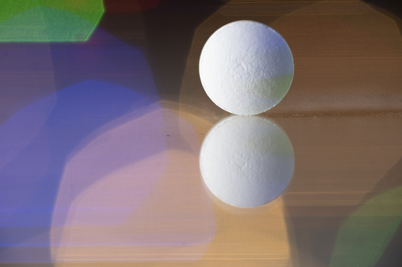 Close-up of a reflected pill on a reflective surface. Colorful lights background.