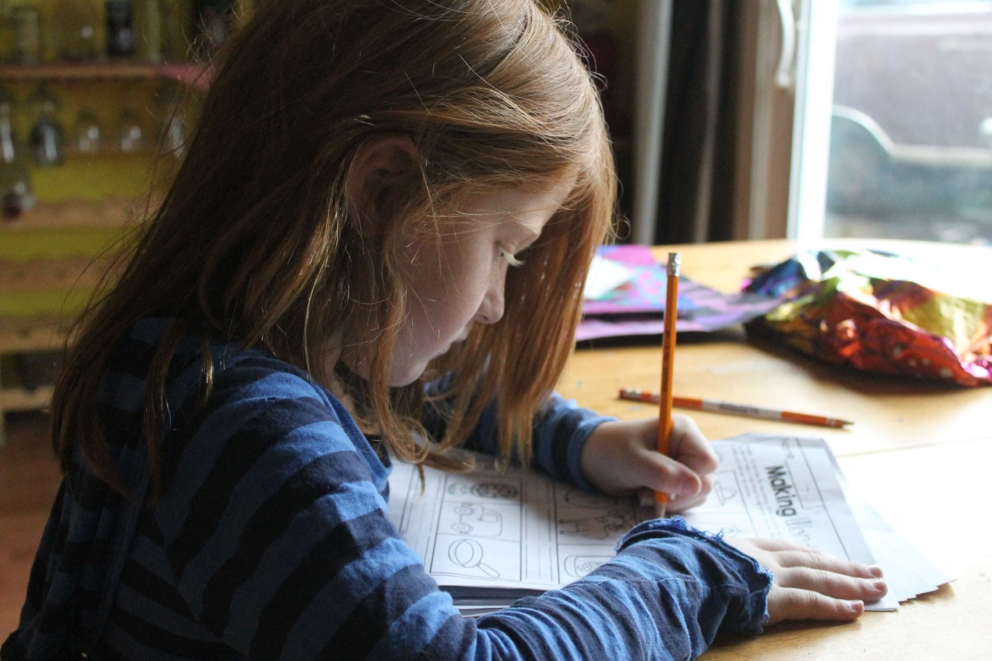 A young red-haired girl sits at a kitchen table completing a worksheet with a pencil.