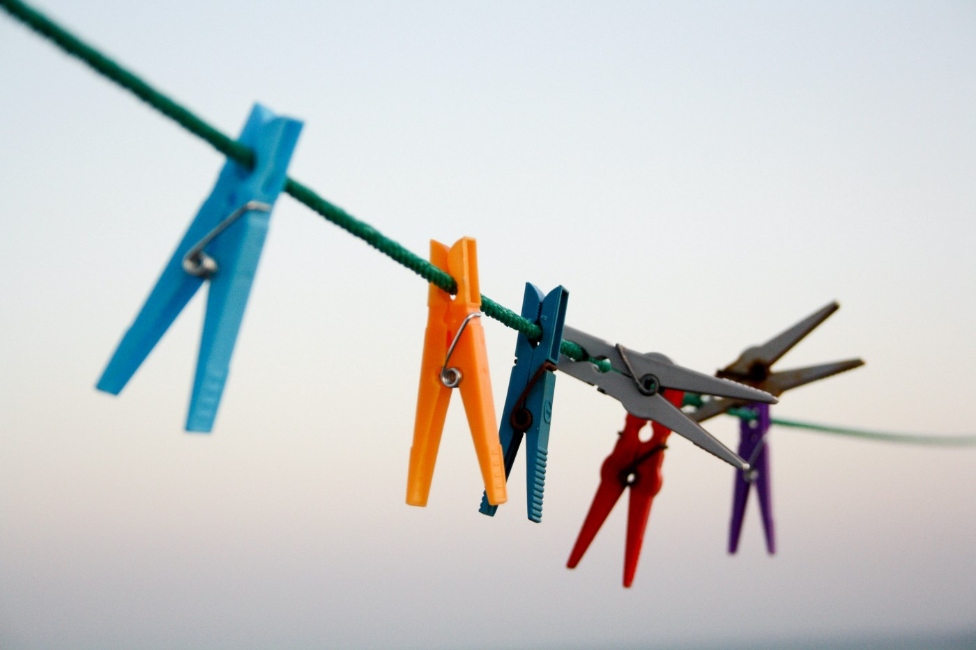 A clothesline with colorful pegs.
