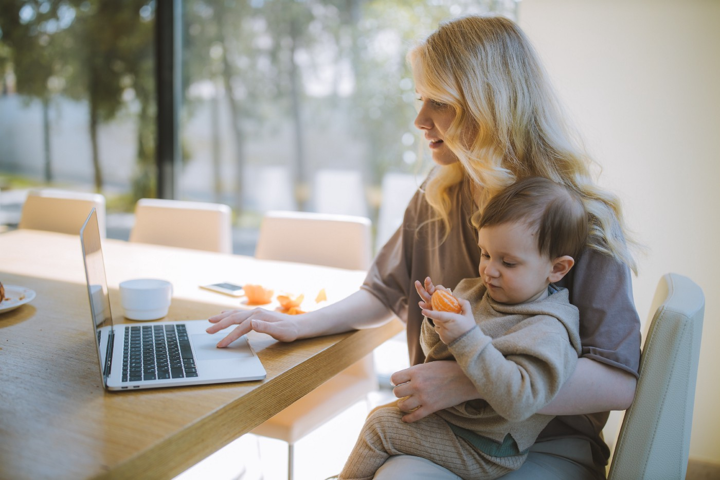 Woman working while holding baby