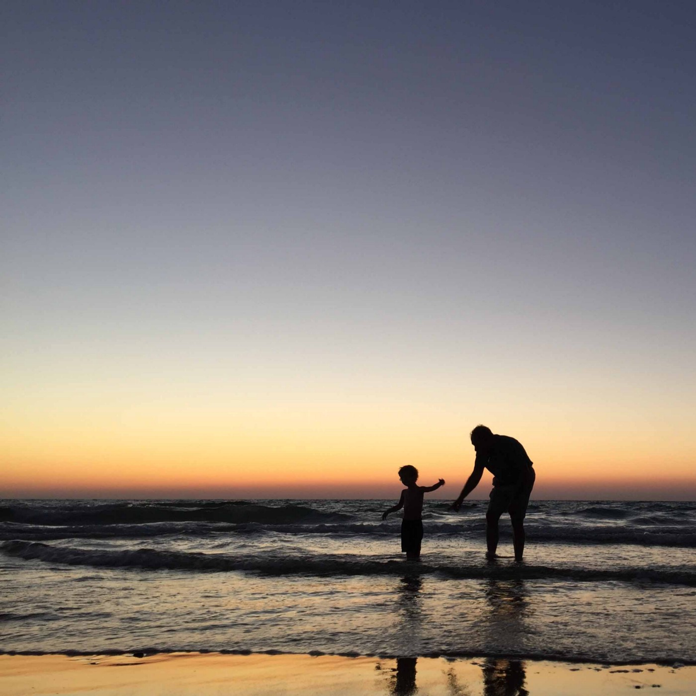 Sillhouette of a father and child on a beach