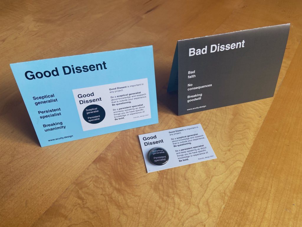 Good Dissent badge in front of folded A5 with Bad Dissent ideas on one side and Good on the other