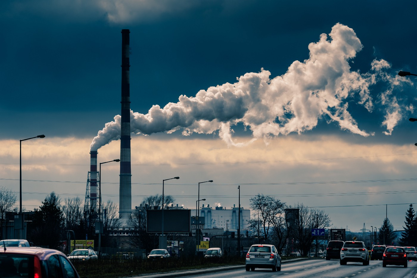 Two tall chimneys pouring thick white smoke over a busy motorway. Blue grey colours. Called Time to Change.
