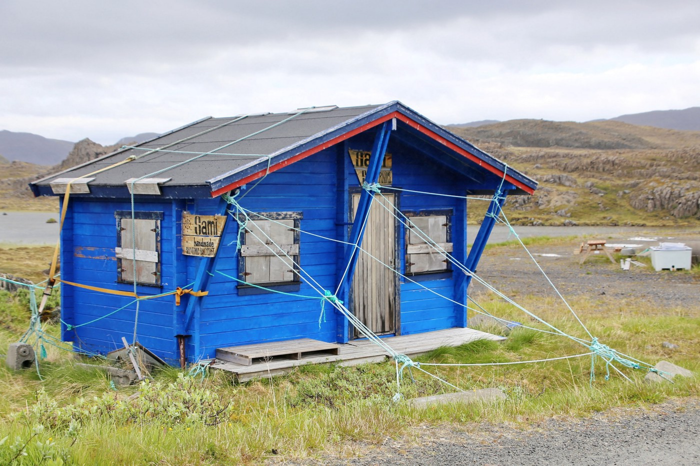 A small, simple blue house stands in the middle of a field, put together by ropes and structure.
