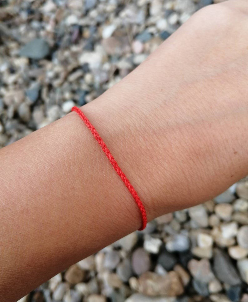 Close up of a wrist wearing a read thread bracelet with beach pebbles in the background