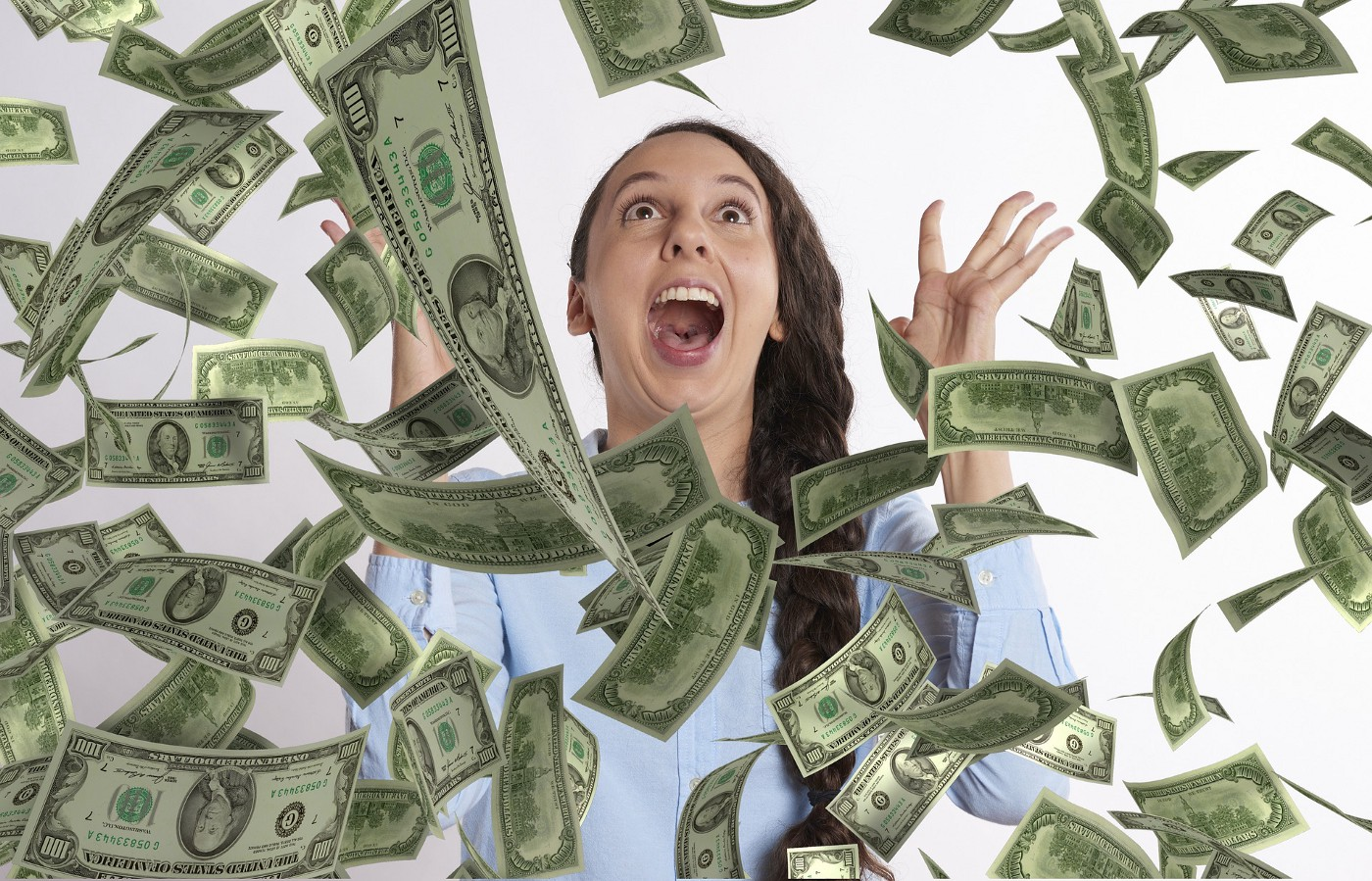 Image of excited woman yelling excitedly as money falls out of the sky