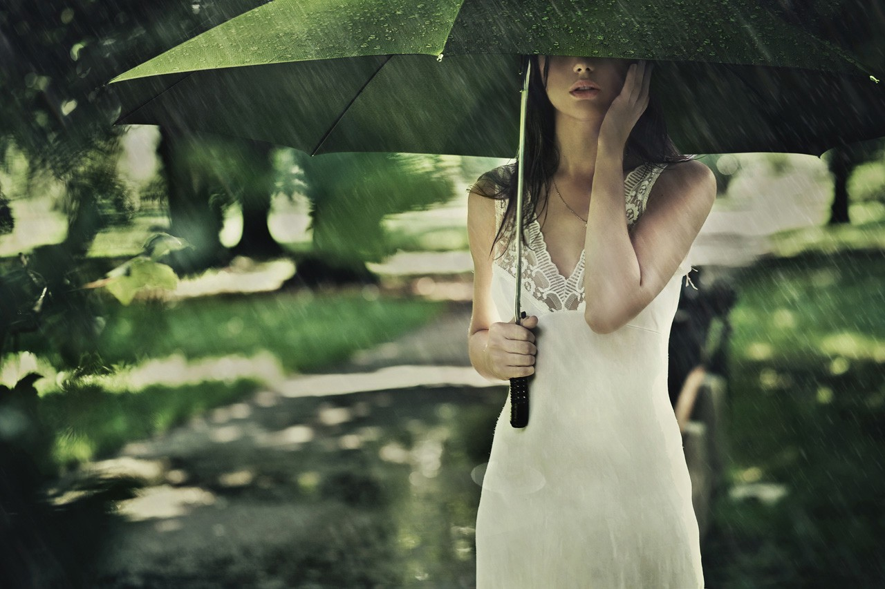 Woman with a green umbrella in the rain