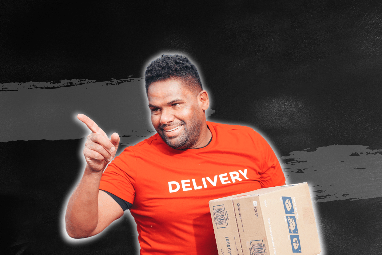 """A man wearing a t-shirt with """"Delivery"""" written on it. He smiles and points to the right direction."""