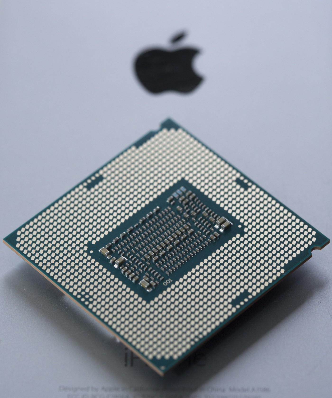 An Intel Core i7 processor on top of a closed Apple laptop with the logo visible.