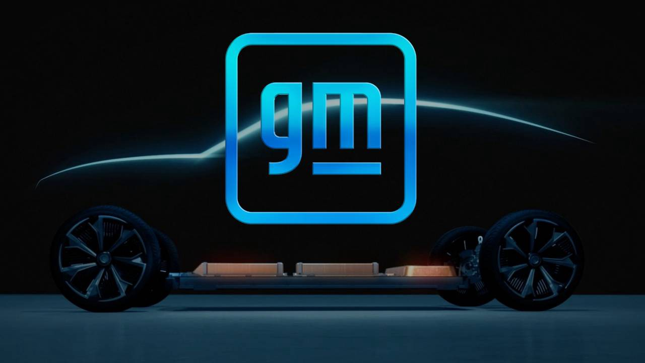 The new General Motors logo in front of a silhouette of a car.