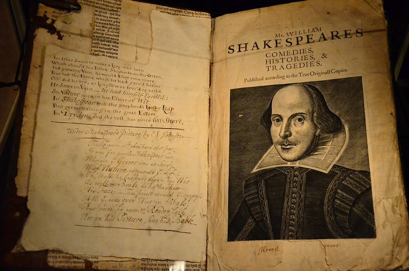 A double-page opening of a large book with faded cream paper. On the right side is an image of William Shakespeare.