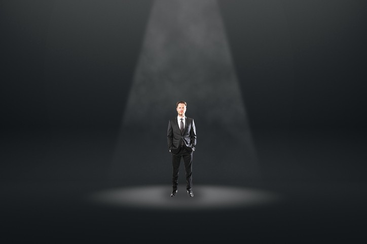 A man dressed in a suit standing underneith a spotlight.