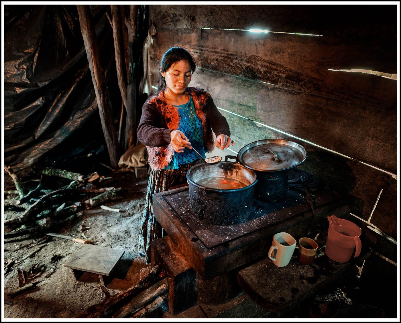 Lucrecia, a young Mayan woman makes a soup next to her wood-burning stove
