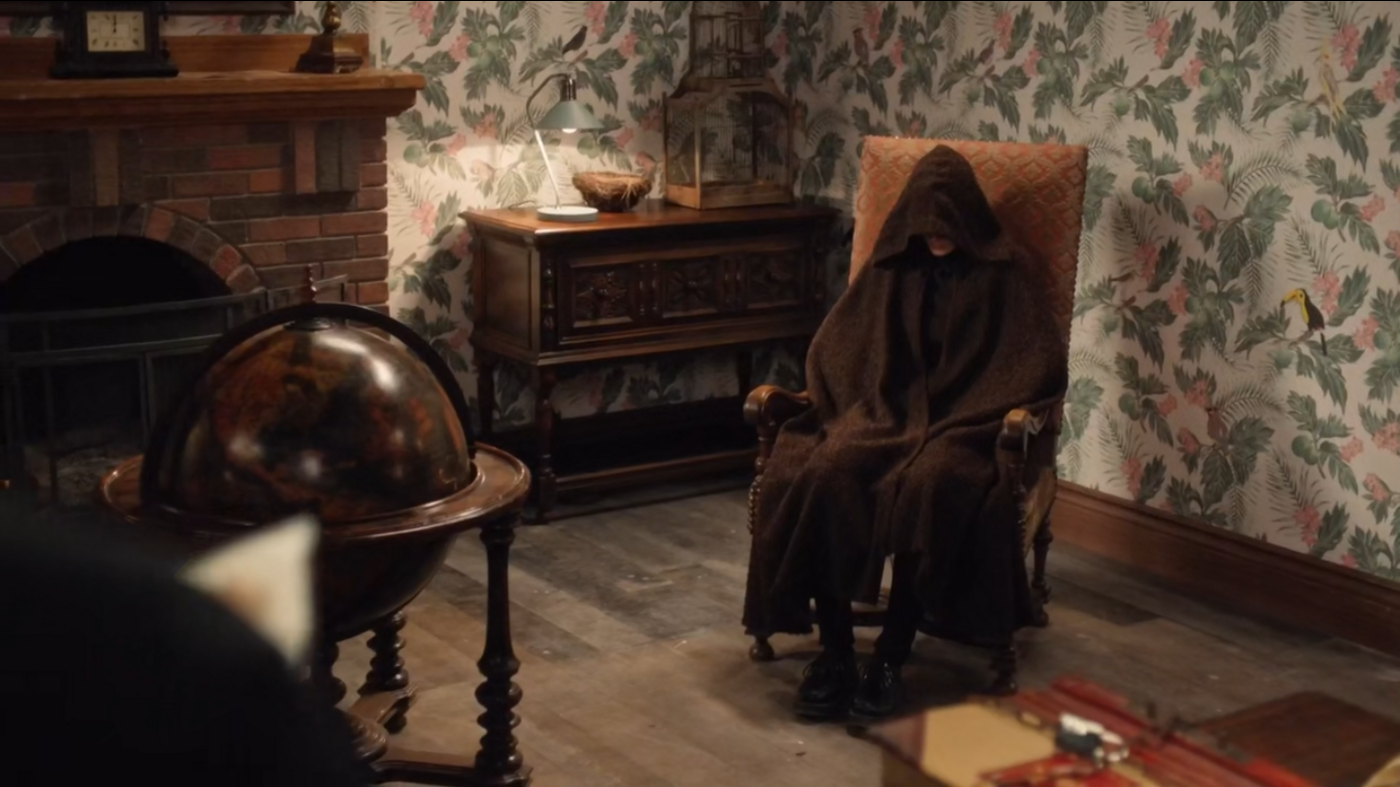 A hooded figure in a chair, face obscured