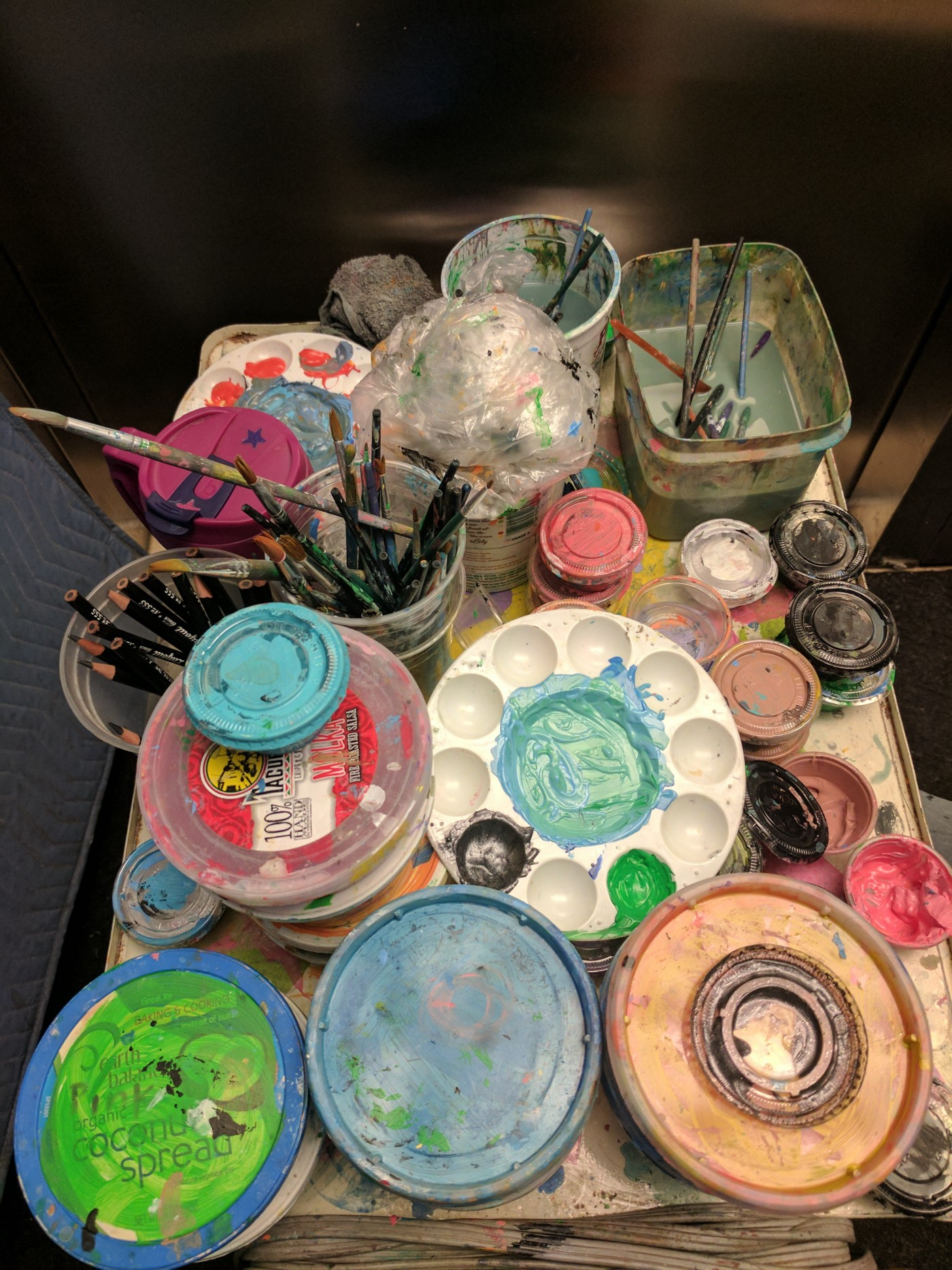 A cluttered cart with paint supplies.