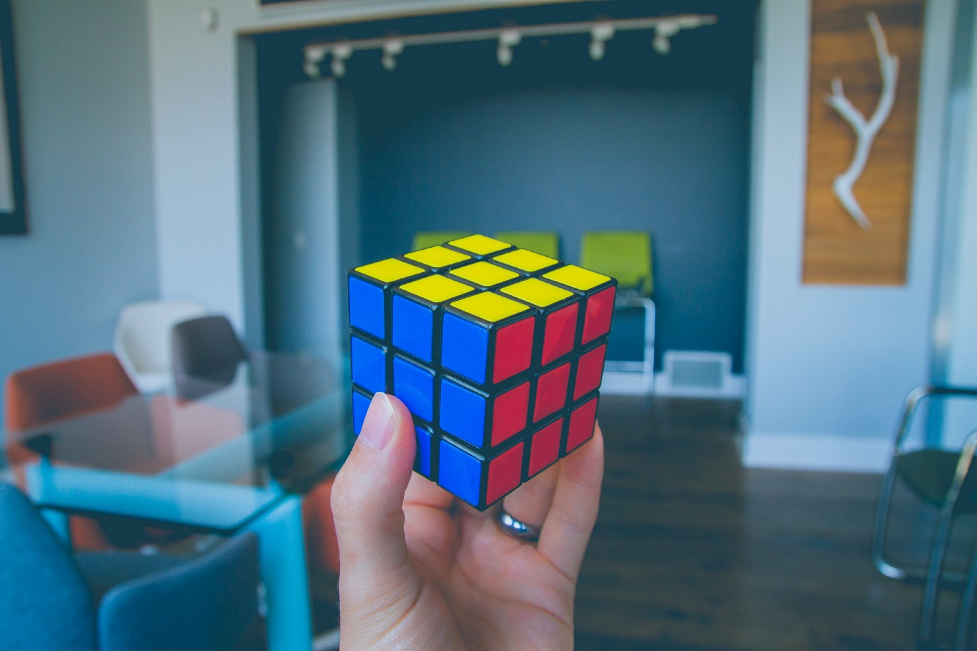 A hand holding up a solved Rubiks Cube.