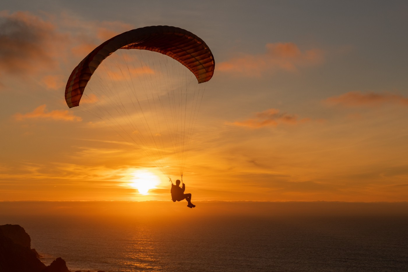 A man paragliding over a sea at sunset