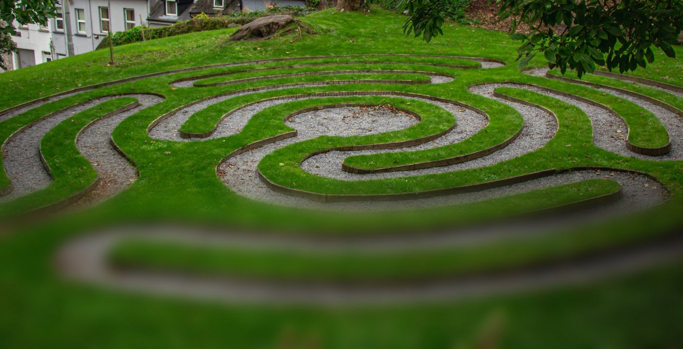 A grassy labyrinth shown in a partially-loaded photo that is clear on the top and blurry at the bottom.