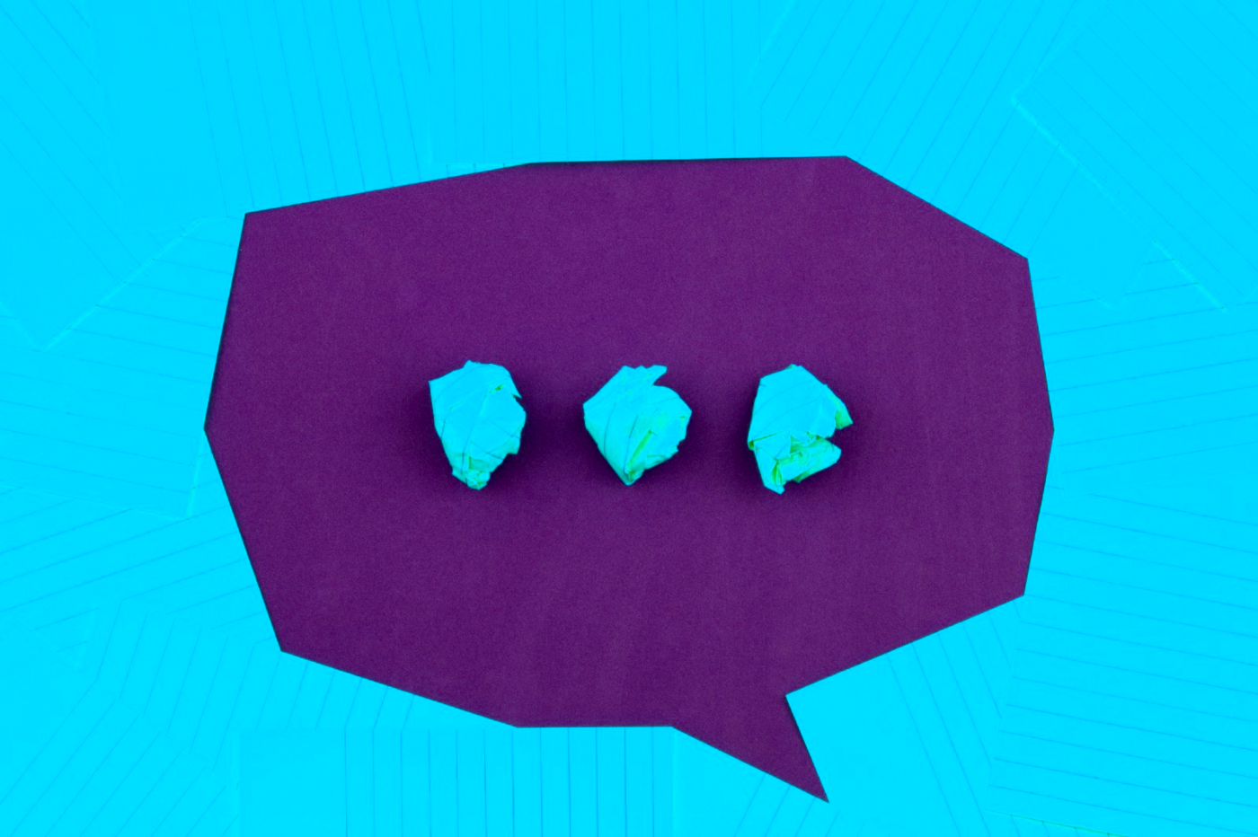 Crumpled pieces of paper in a speech bubble.