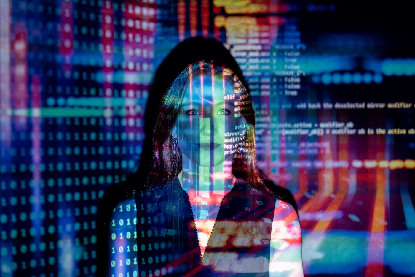 woman standing in front of projection of code on a screen