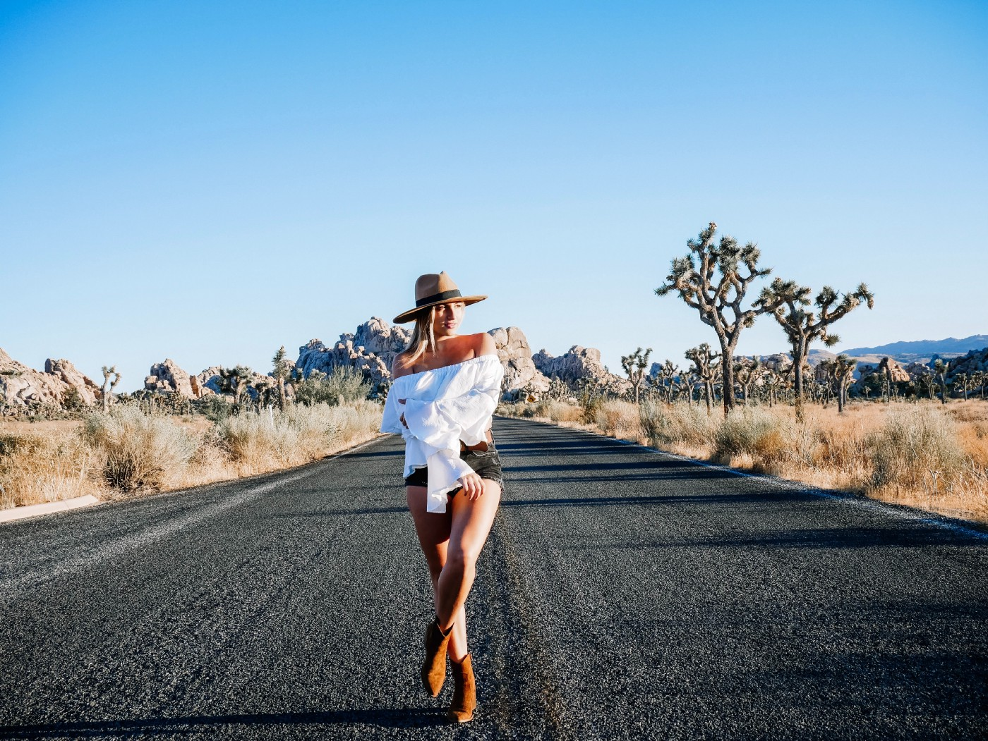 White woman in white shoulderless top and shorts, brimmed hat and boots, standing in the middle of a road in Joshua Tree Park
