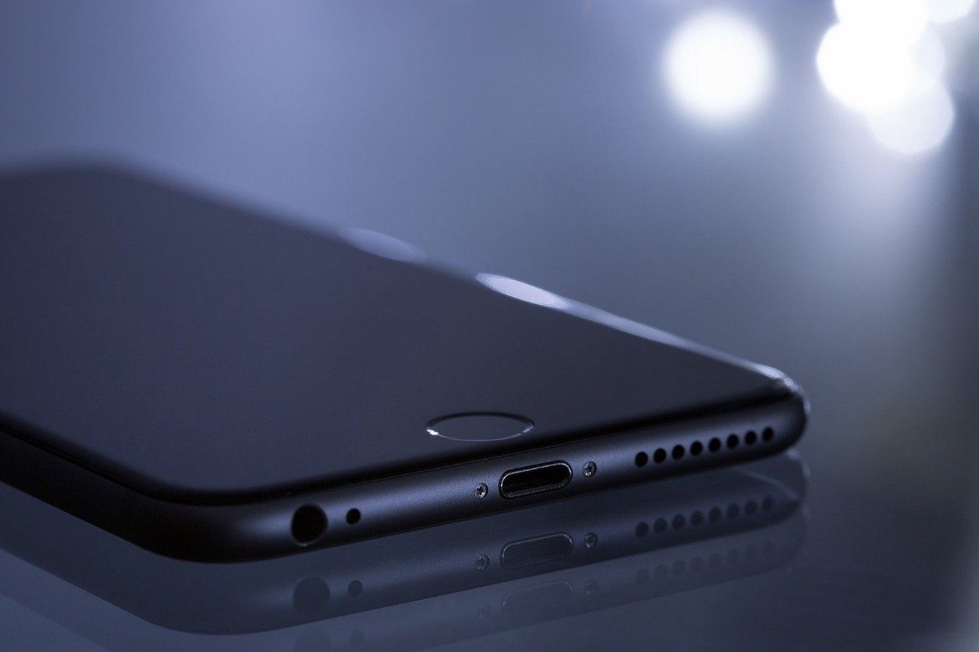 Color photo of a black mobile phone, face down on a surface. Bright lights in the background of otherwise darkness.