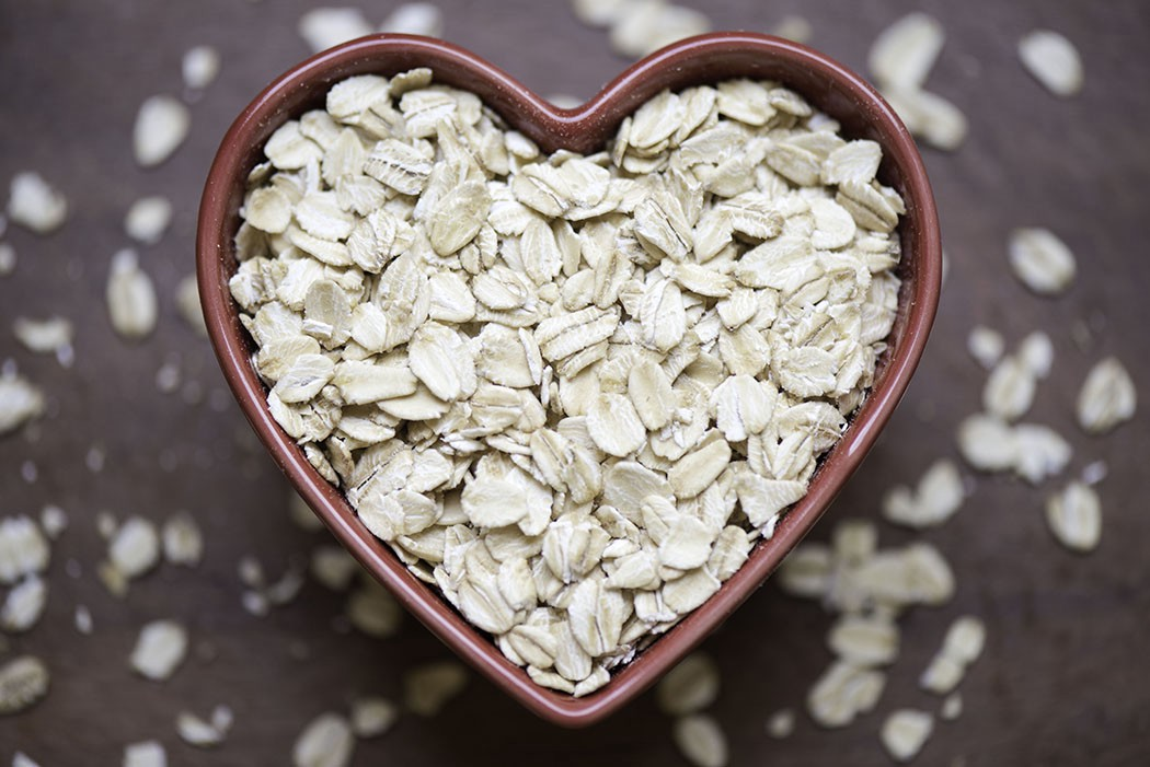 A close up of red heart shaped bowl filled with rolled oats.