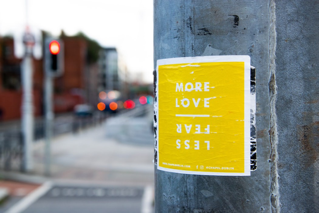 """an image of a yellow poster that says """"more love"""" """"less fear"""" on a wall"""