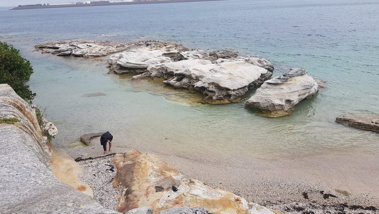 La Peruse Beach, Sydney Australia. There is seafoam green water surrounding white rocks. It is the edge of the cliff.