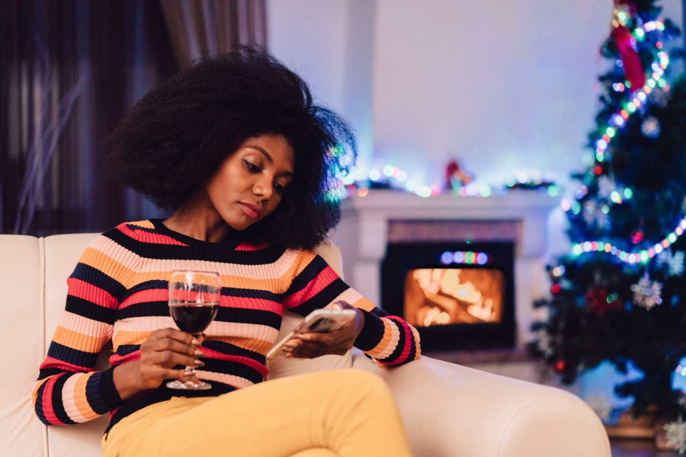 Bored woman looking at her phone holding a wine glass.