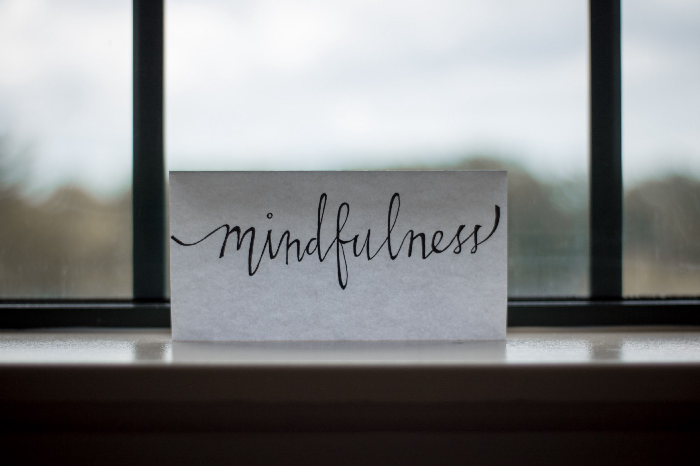 """Paper with """"mindfulness"""" handwritten on it in front of a blurry window."""