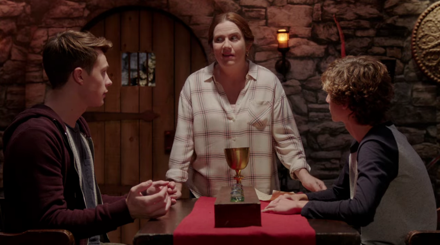 A white mother looks at her two teen boys, who are seated at a table in front of her, with an exasperated expression on her face.