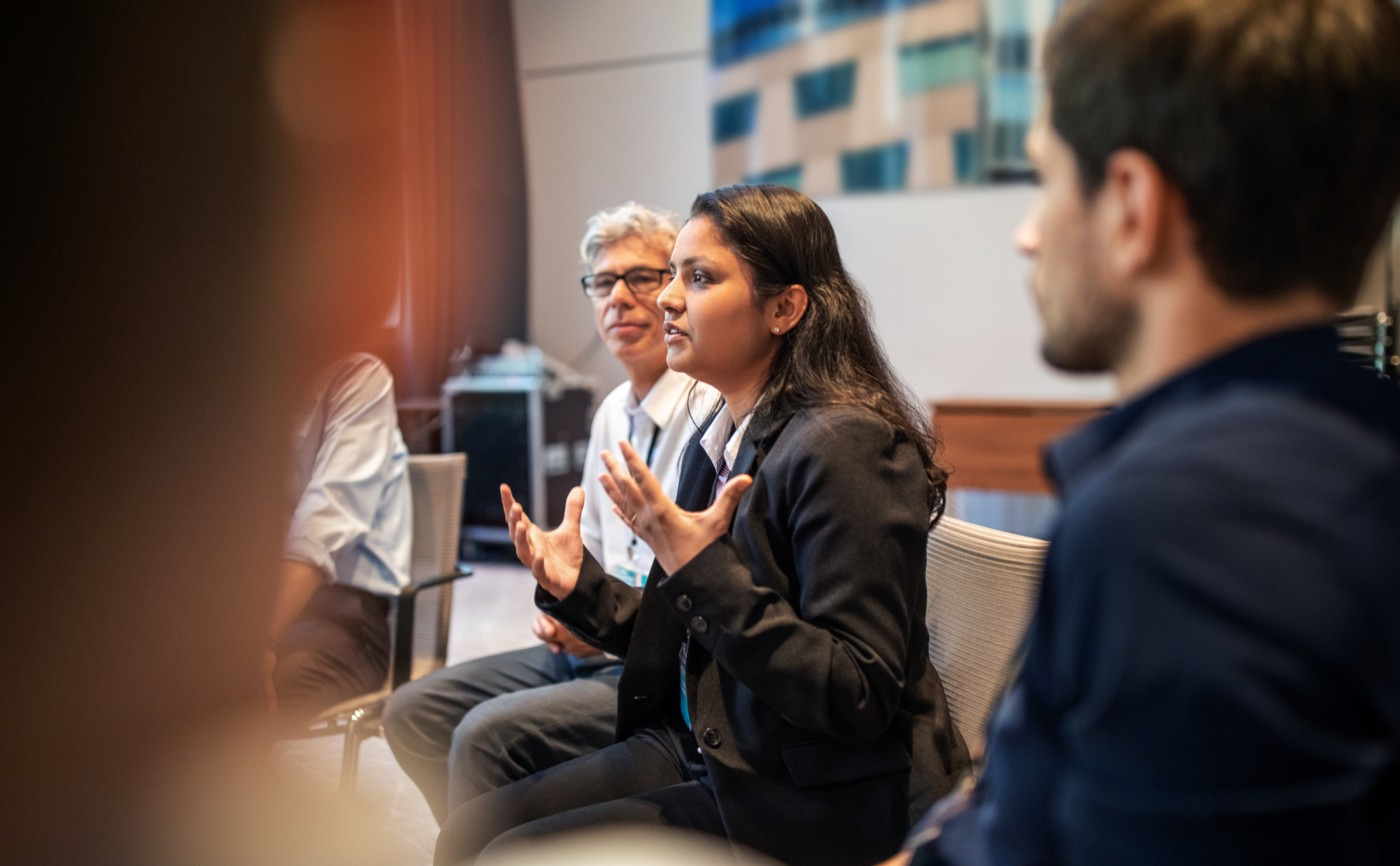 A South Asian female executive explaining strategy to her white male colleagues in a meeting.