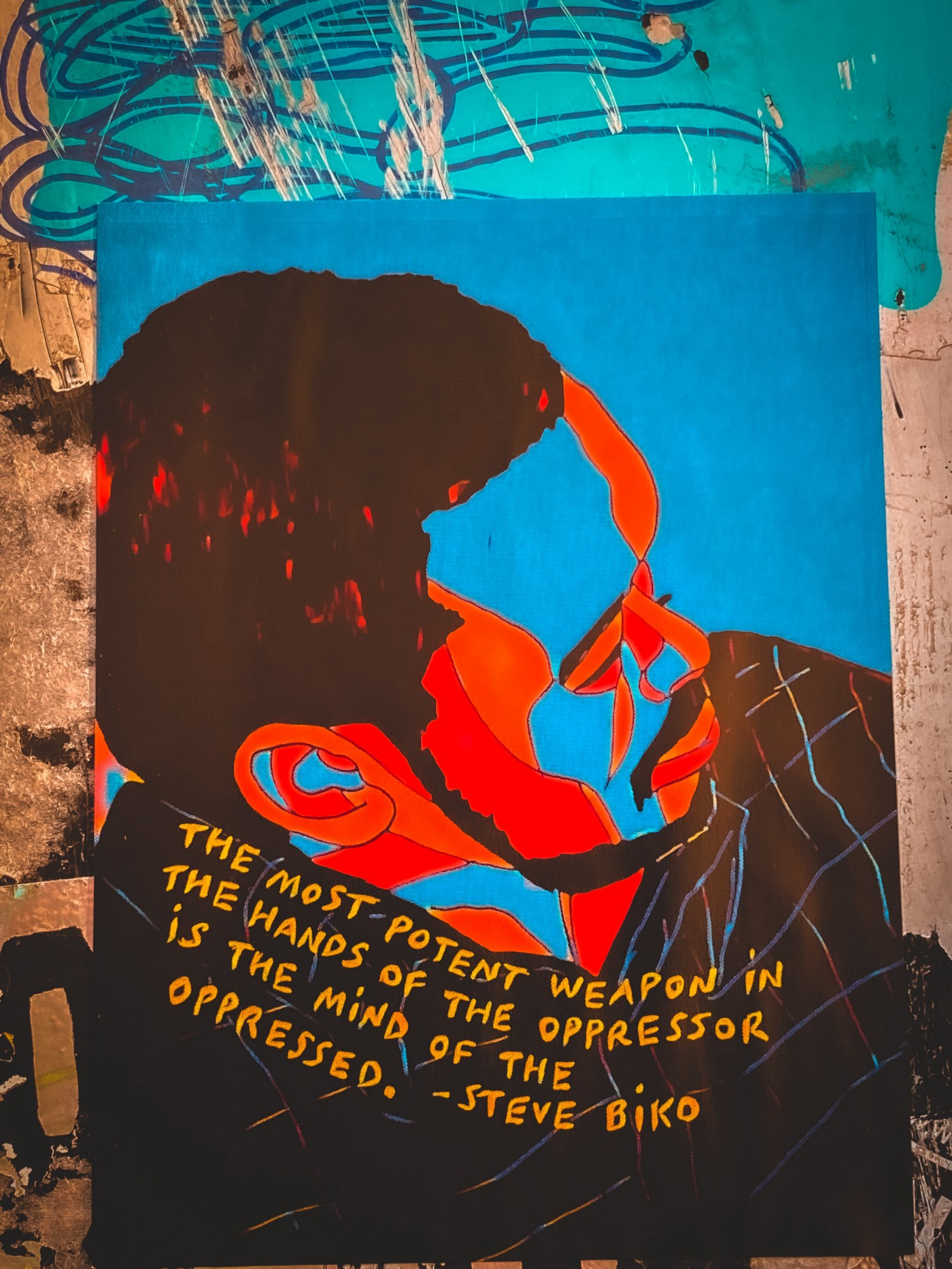 A Poster on the wall of a man with a red and blue painted face.