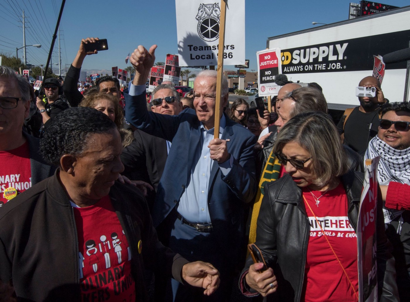 Joe Biden holding a pro-union sign and giving a raised thumbs-up, surrounded by pro-union demonstrators outdoors.