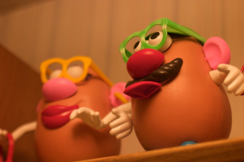 Two Potato Head toys on a shelf. On the left is Mrs. Potato Head, her pupils not visible behind her yellow-rimmed glasses. On the right is Mr. Potato Head, wearing neon green glasses and sticking out his tongue.