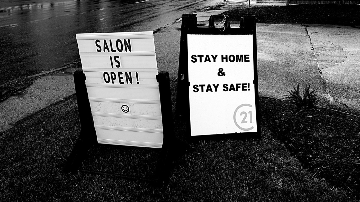"2 signs by the side of the road. 1 says, ""Salon is open!"" and the other says, ""Stay home and stay safe!"""