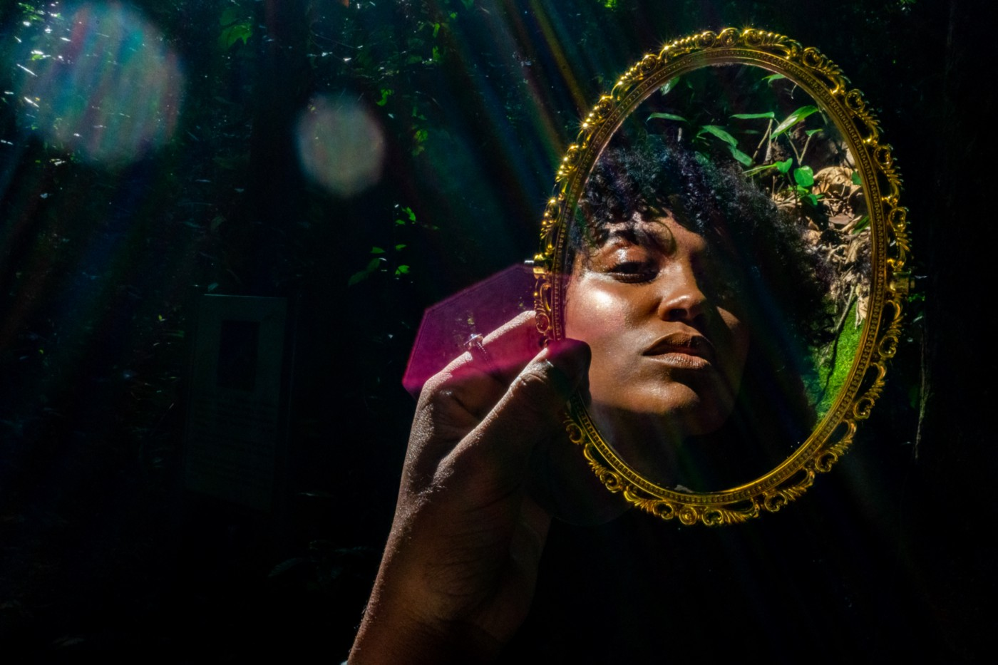 Young Black woman holding up and looking into a gilded mirror in the forest.