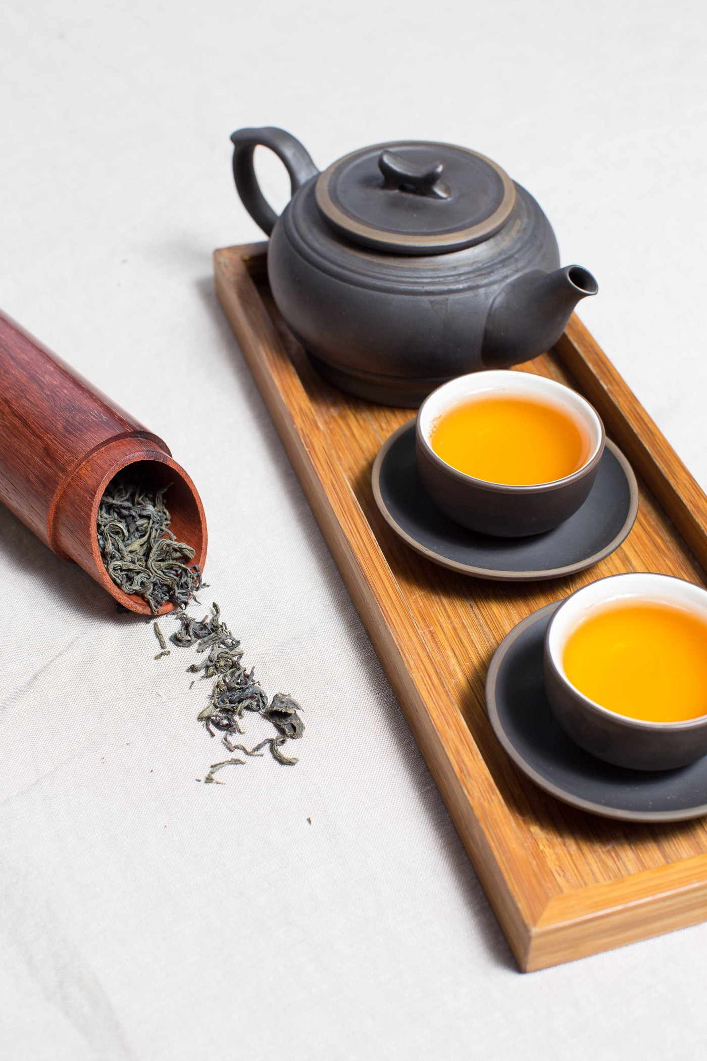 Photo of a teapot with two cups and a bamboo tea leaf holder