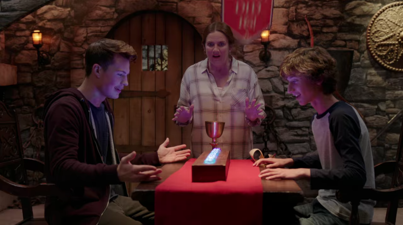 The white mother and her two teen boys look at a row of lit-up gemstones on the table in front of him. They're all raising their hands excitedly, reacting to the gemstones lighting up