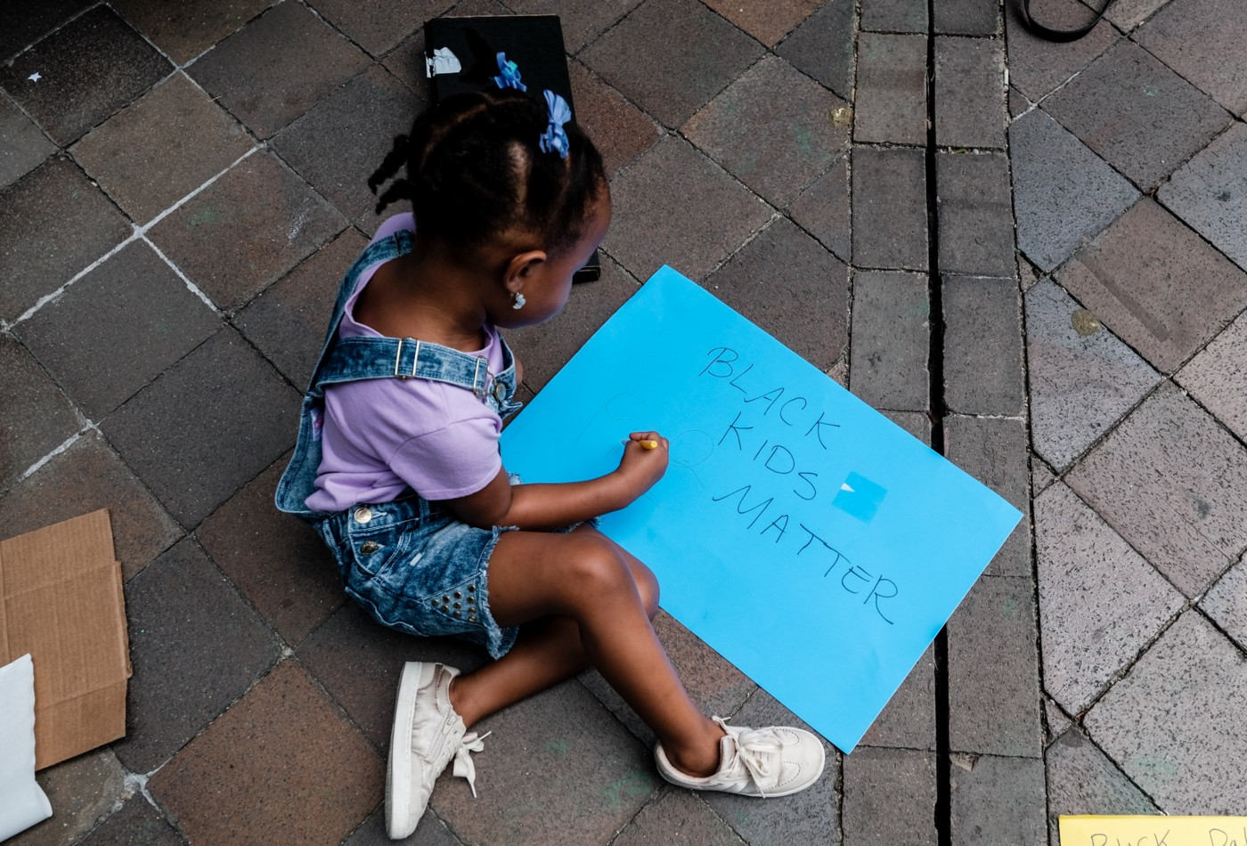 "A young Black girl sits on the ground with a bright blue sign that says ""Black Kids Matter."""