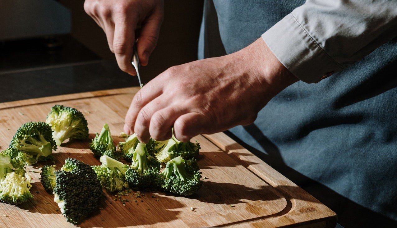 A close-up of a man chopping broccoli