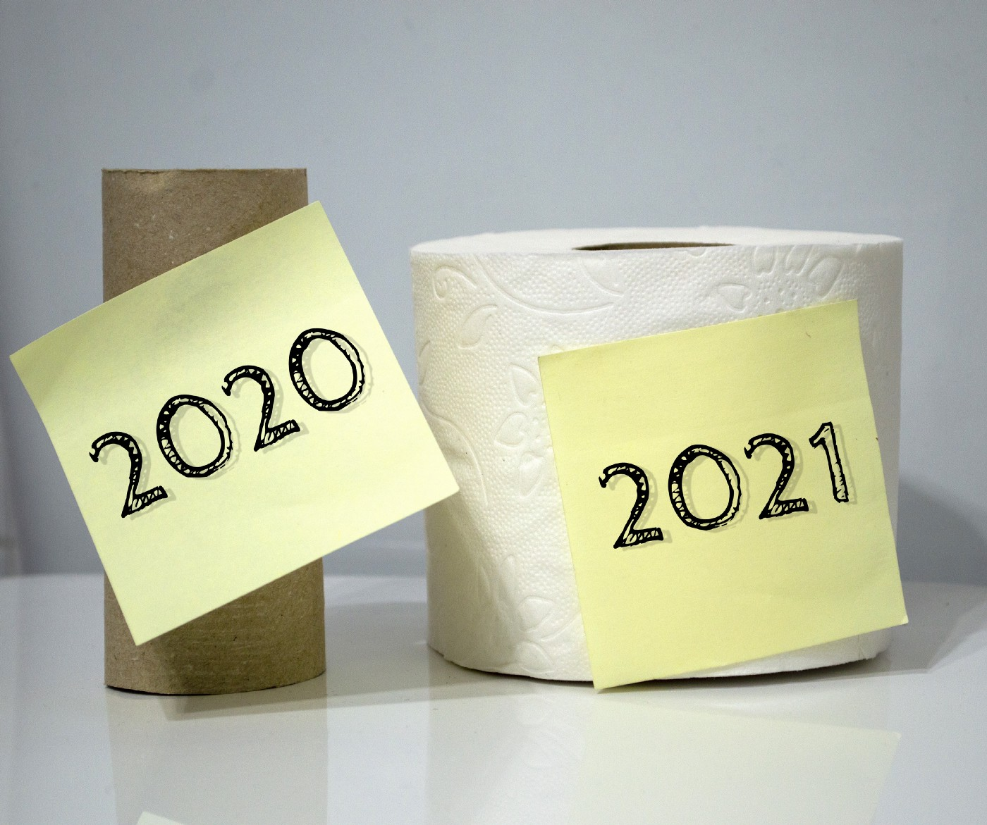 An empty toilet paper roll with post-it with 2020. to its right: a new roll with a post-it with 2021